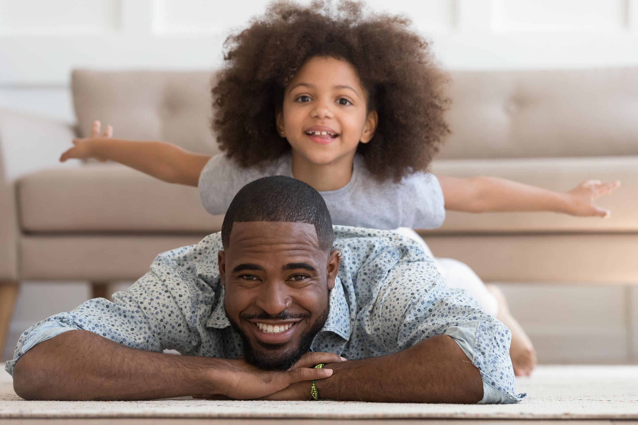 Happy african american joyful family of two portrait. Cheerful smiling black father lying on floor carpet, carrying little cute mixed race daughter, pretending to be plane, on back looking at camera.